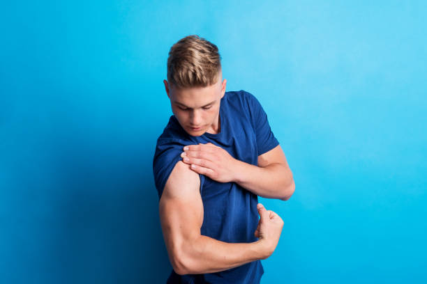 Portrait of a cheerful young man in a studio, flexing muscles. Portrait of a young cheerful man in a studio standing on a blue background, flexing muscles. bicep stock pictures, royalty-free photos & images