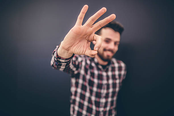 Portrait of a cheerful young man showing okay gesture isolated stock photo