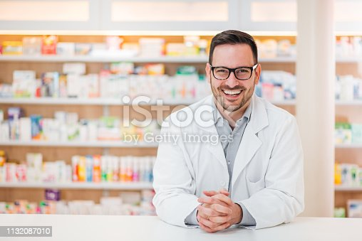 Portrait of a cheerful young pharmacist leaning on a counter at drugstore, looking at camera.