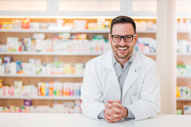 Portrait of a cheerful young pharmacist leaning on a counter at drugstore, looking at camera. stock photo