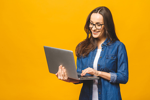 Portrait of a cheerful young woman wearing casual standing isolated over yellow background, holding laptop.