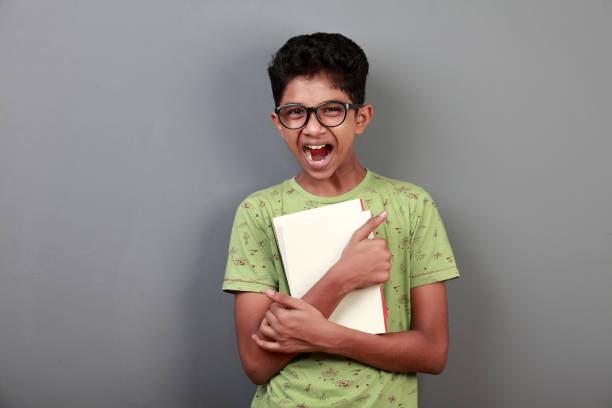 Portrait of a cheering boy of Indian origin holding books in his hand stock photo