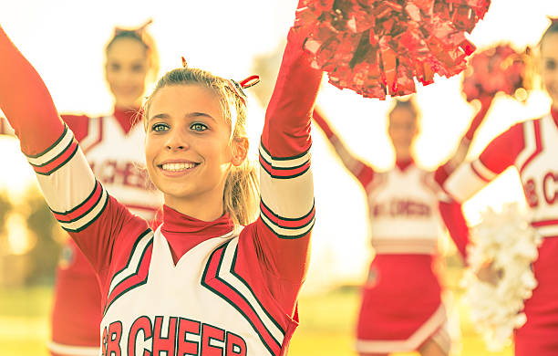 portrait of a cheerleeder in action - high school sports stock pictures, royalty-free photos & images