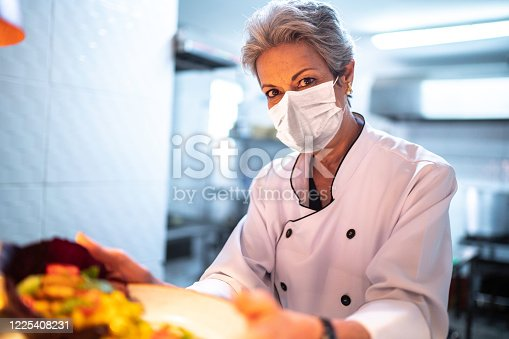 Portrait of a chef showing his ready dish using protective mask