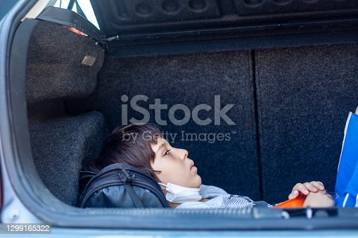 Portrait of a cute child playing outdoors in car's luggage.