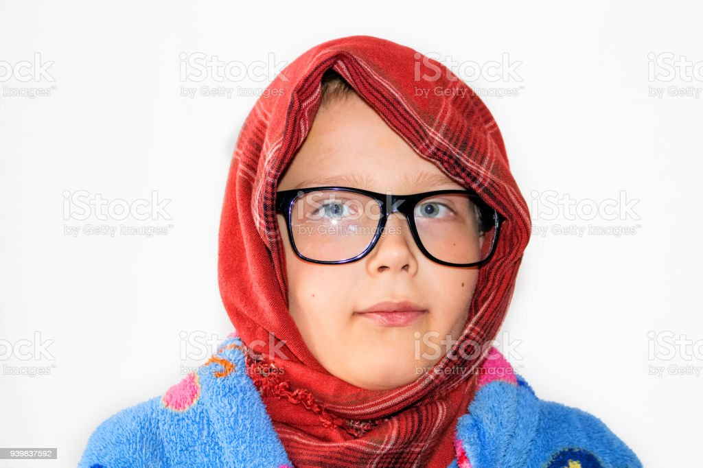 Portrait of a child on a white background.  A headscarf, glasses, a smile, a pensive look on my head. stock photo