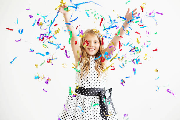 Portrait of a child throws up multi-colored tinsel and confetti stock photo