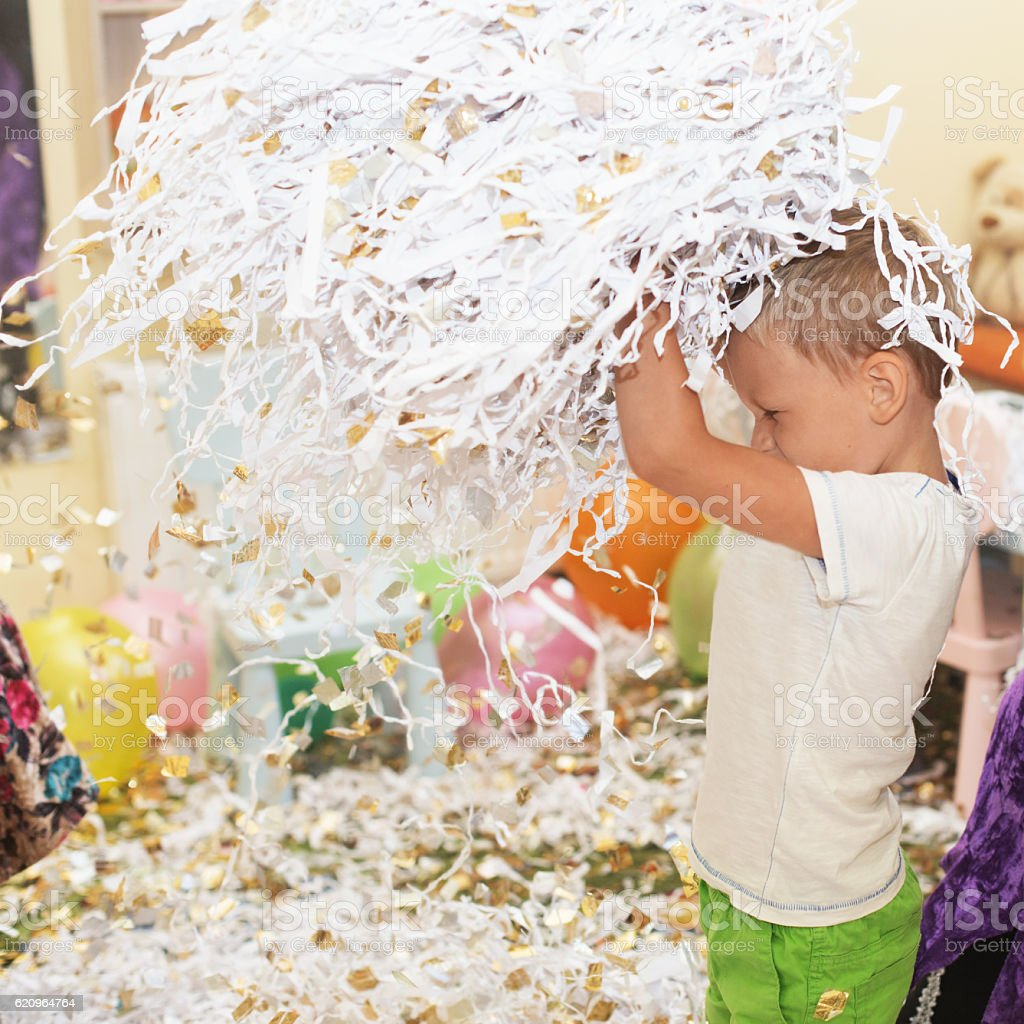 Portrait of a child throws up multi-colored tinsel stock photo
