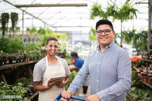 Portrait of a client using a shopping cart buying plants