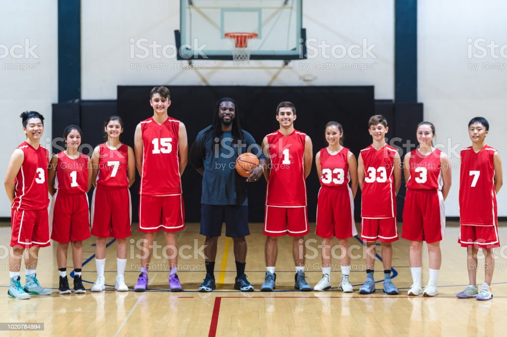 Coach stands in the middle of his co-ed high school basketball team....
