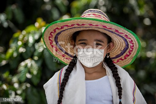 """Portrait of a Colombian peasant girl at a coffee farm wearing a facemask to avoid the coronavirus and looking at the camera smiling -"""" Pandemic lifestyle concepts"""