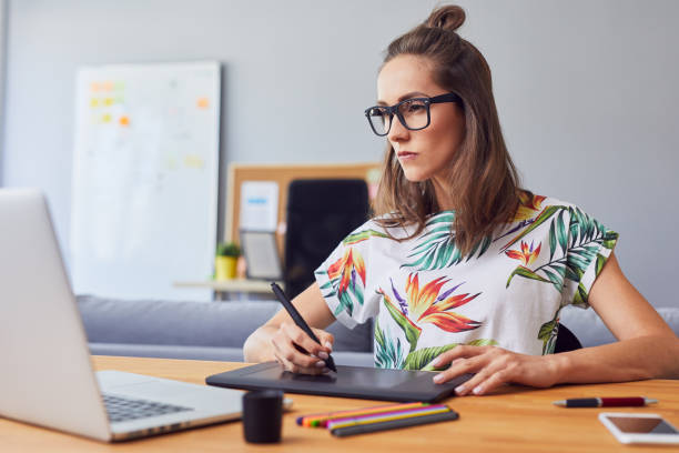 Portrait of a concentrated female graphic designer working in her office Portrait of a concentrated female graphic designer working in her office illustrator stock pictures, royalty-free photos & images
