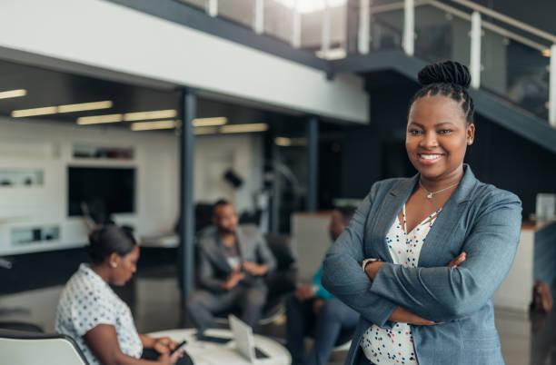 porträtt av en säker svart affärskvinna med alla afrikanska amerikanska team i bakgrunden - afrika bildbanksfoton och bilder