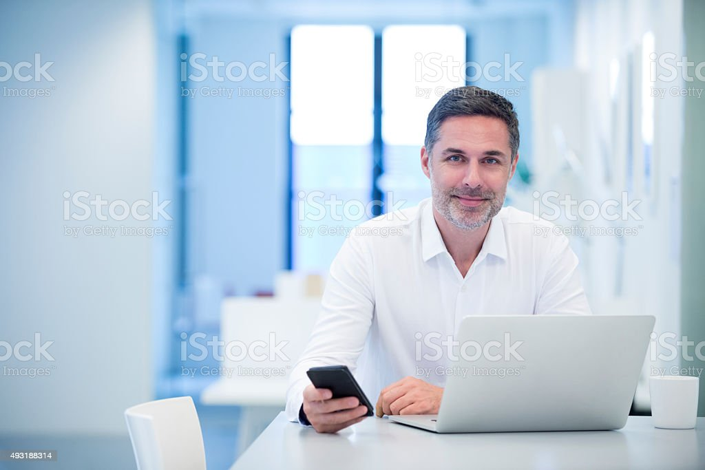 Portrait of a confident businessman sitting at laptop stock photo