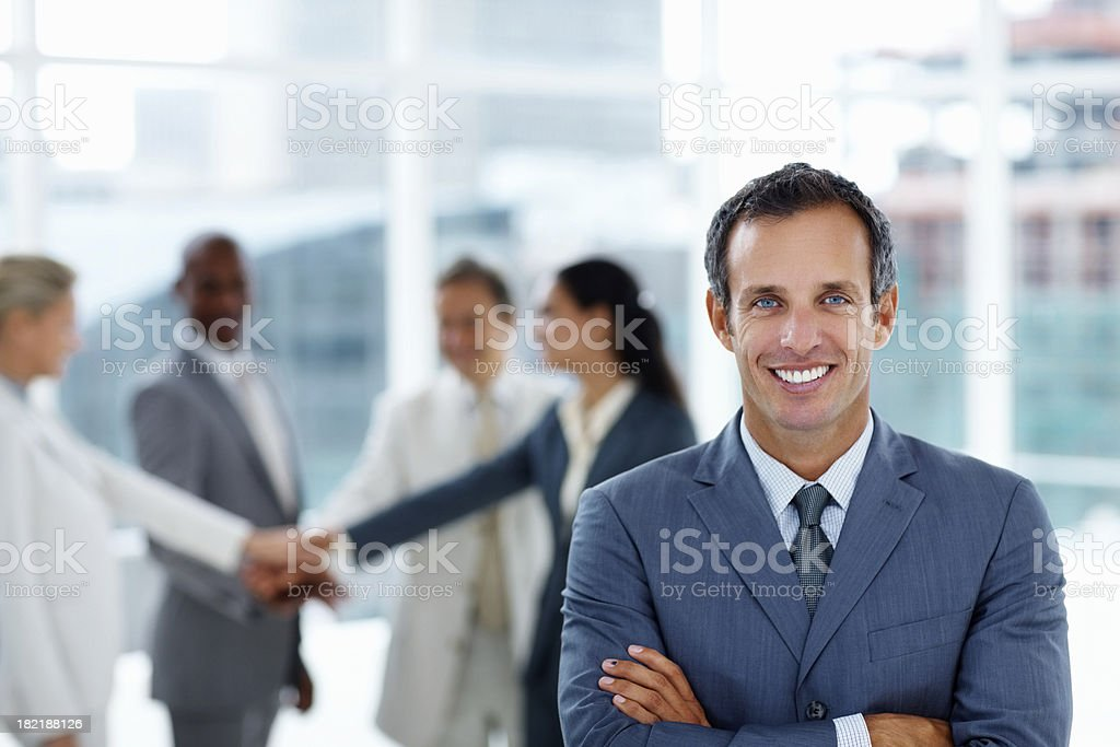 Portrait of a confident businessman with colleagues in the background royalty-free stock photo