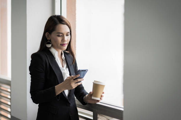 Portrait of a confident businesswoman in business suit holding a cup of coffee while using cellphone during break-time in the business building. Business stock photo. stock photo