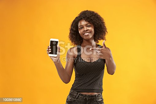 1159261513 istock photo Portrait of a confident casual afro girl showing blank screen mobile phone 1003610592