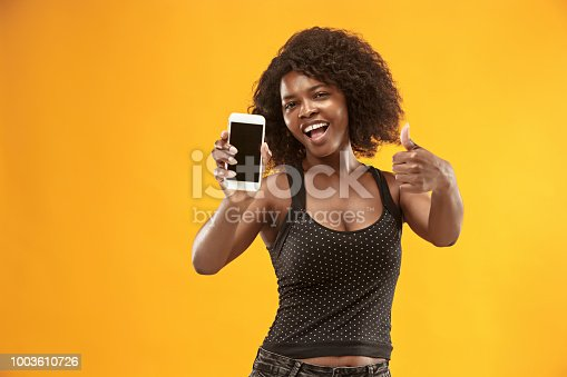 1159261513 istock photo Portrait of a confident casual afro girl showing blank screen mobile phone 1003610726