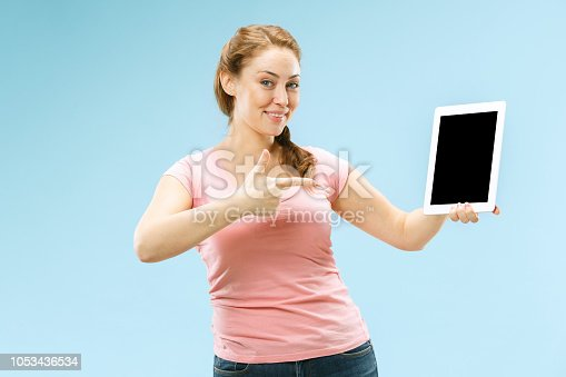 863476202istockphoto Portrait of a confident casual girl showing blank screen of laptop isolated over blue background 1053436534