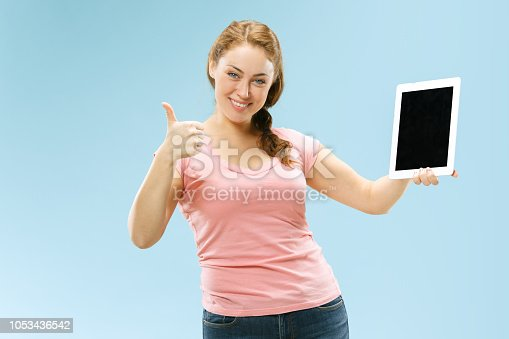 863476202istockphoto Portrait of a confident casual girl showing blank screen of laptop isolated over blue background 1053436542
