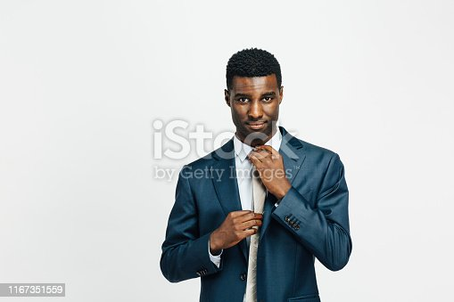 istock Portrait of a confident man in business suit, fixing his tie 1167351559