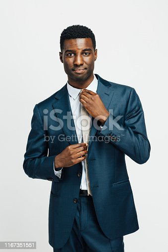 istock Portrait of a confident man in business suit, fixing tie 1167351551