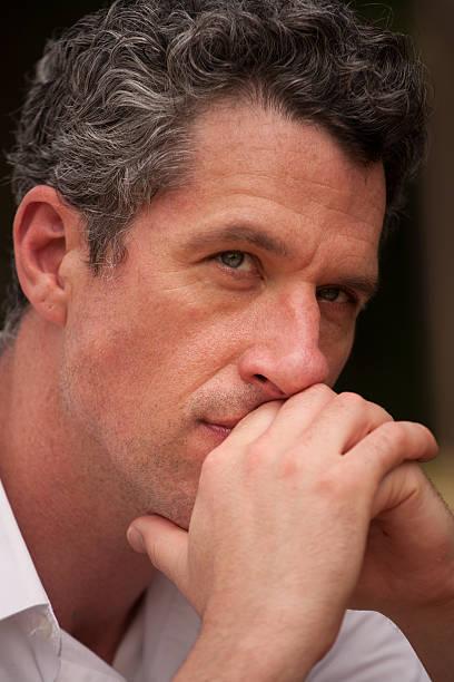 portrait of a confident professional man deep in thought - foto's van hands stockfoto's en -beelden