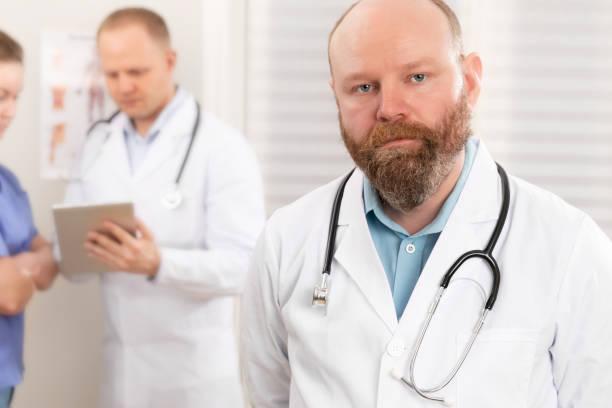 Porträt eines selbstbewussten echten Arztes, der vor seinem Gesundheitsteam steht – Foto