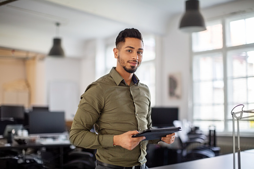 Portrait of young businessman standing in office with digital tablet in hand. Male professional looking at camera.