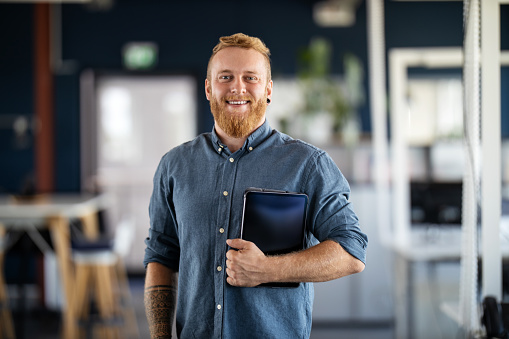 Portrait of a businessman with beard standing in office holding digital tablet. Confident male business executive in office looking at camera.