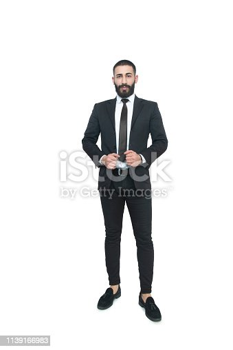 Portrait of a confident young businessman standing over white background. Vertical composition. Studio shot.