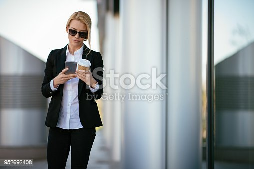 Portrait of a confident young businesswoman talking on cell. Shallow DOF. Developed from RAW; retouched with special care and attention; Small amount of grain added for best final impression. 16 bit Adobe RGB color profile.