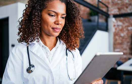 Portrait of an attractive young african-american female doctor in white coat. Portrait of glad smiling doctor in white uniform standing near staircase in doctor's office and using digital tablet.