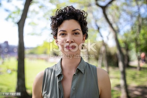 Portrait of a confident young woman standing at the park. Beautiful female in casuals looking at camera.