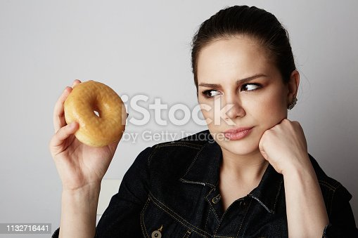 692840848istockphoto Portrait of a confused beatiful caucasian woman thinking to eat donut or not isolated over white background. 1132716441