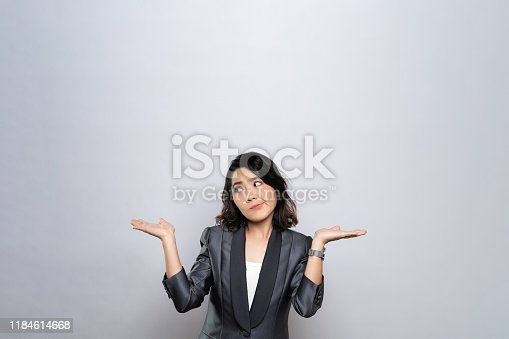 istock Portrait of a confused woman isolated over white background 1184614668