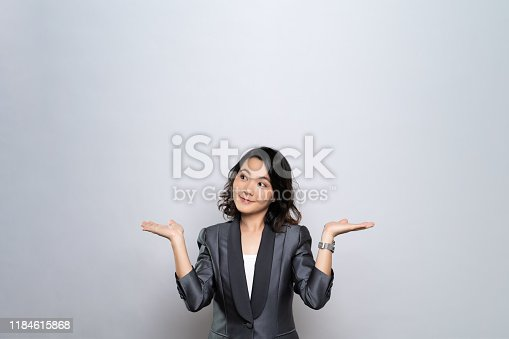 istock Portrait of a confused woman isolated over white background 1184615868