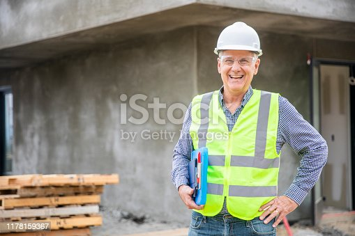 A senior construction site manager visually inspects a building project