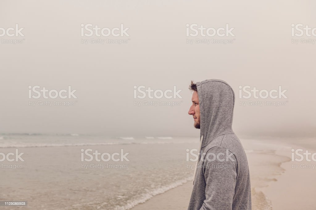 Portrait of a contemplative man at the waters edge of Fistral Beach, Newquay, Cornwall on a misty Autumn day. stock photo