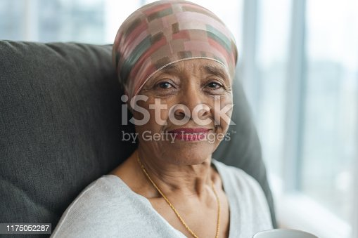 A black senior woman with cancer is wearing a scarf on her head. She is sitting at home in her living room. She is smiling thoughtfully at the camera. She is full of gratitude and hope for recovery.