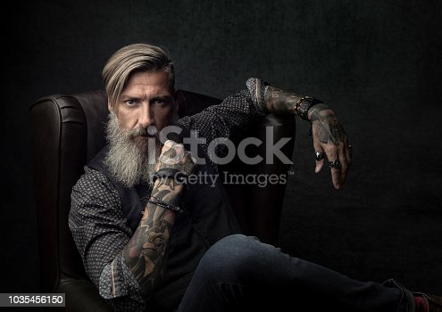 istock Portrait of a cool bearded businessman, who is sitting on an armchair 1035456150