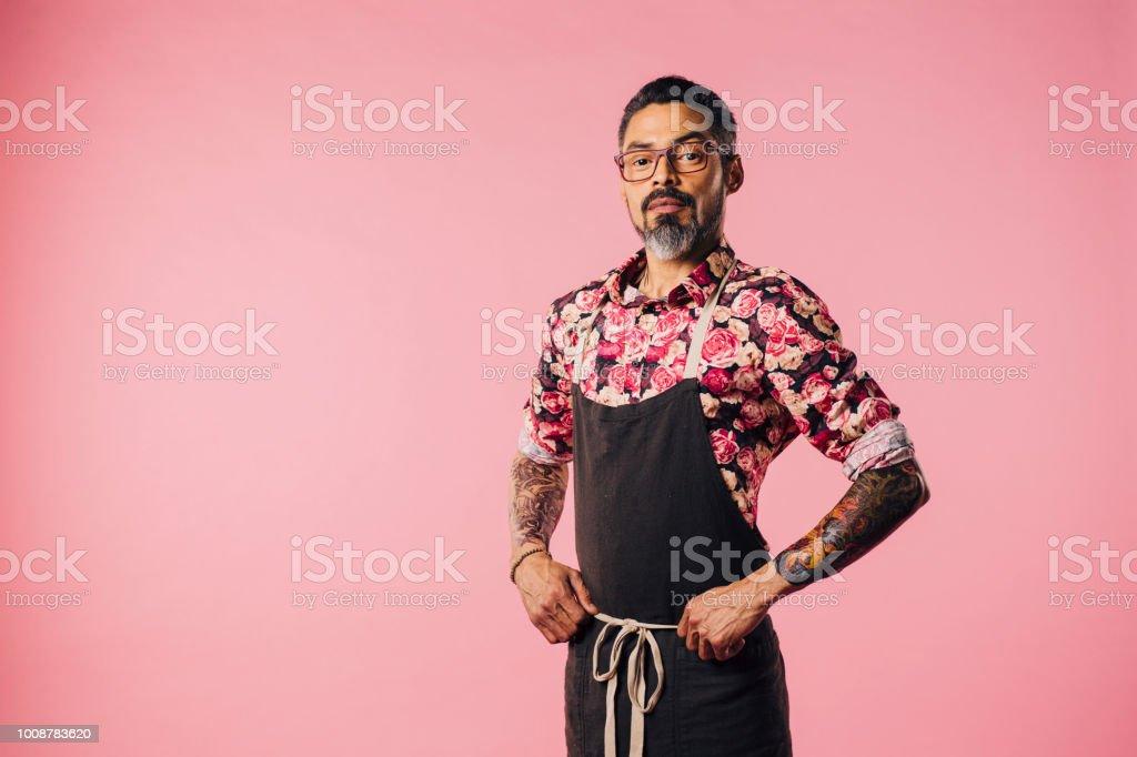 Retrato de uma cook cool com tatuagens com as mãos na cintura - foto de acervo
