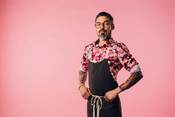 porträt von cool cook mit tattoos mit händen auf taille - alte tattoos stock-fotos und bilder