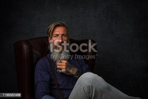 istock Portrait of a cool modern pensive bearded businessman, who is sitting in an armchair 1135332458