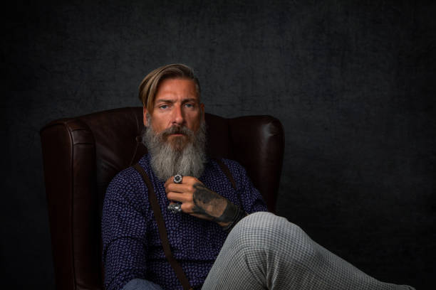 Portrait of a cool modern pensive bearded businessman, who is sitting in an armchair stock photo
