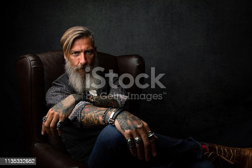 istock Portrait of a cool modern pensive bearded businessman, who is sitting in an armchair 1135332652