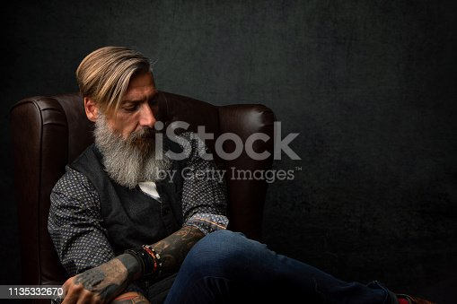 istock Portrait of a cool modern pensive bearded businessman, who is sitting in an armchair 1135332670