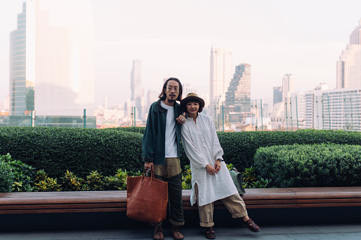 Cute young Asian couple looking at camera, wide angle view.