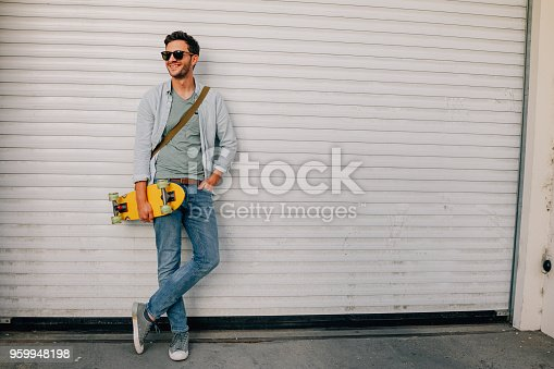 Portrait of a young hip man, who is using his skateboard as a mean of transportation all over the city