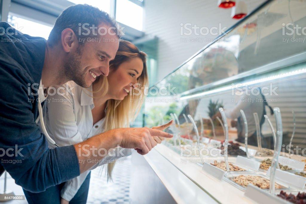 Portrait of a couple at an ice cream shop choosing a flavor stock photo